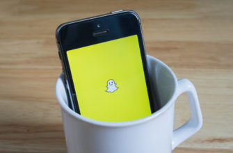 Apple iPhone5s in a mug showing its screen with Snapchat logo